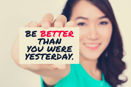 yesterday: BE BETTER THAN YOU WERE YESTERDAY, message on the card shown by a woman,  vintage tone