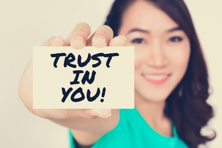 trustworthiness: TRUST IN YOU!, message on the card shown by a woman,  vintage tone