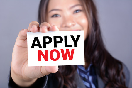 vacant sign: APPLY NOW, message on the card shown by a woman