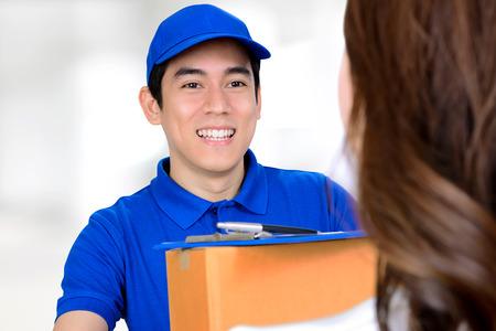 delivering: Smiling delivery man delivering a package