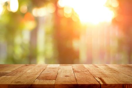 Houten tafelblad op blur achtergrond van het zonlicht schijnt door de bomen - kan worden gebruikt voor weergave of montering uw producten