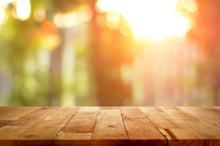 Wood table top on blur bokeh background of sunlight shining through the trees - can be used for display or montage your products