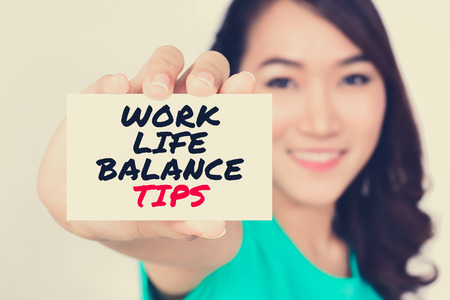 life balance: WORK LIFE BALANCE TIPS message on the card shown by a woman, vintage tone image
