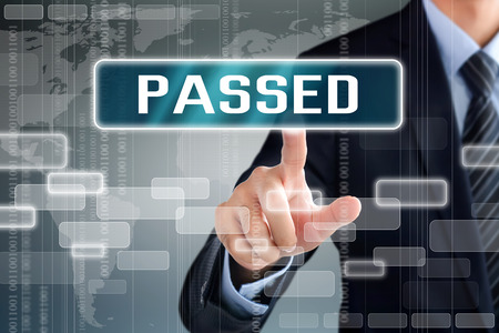 passed test: Businessman hand touching PASSED sign on virtual screen