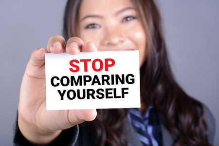 card stop: STOP COMPARING YOURSELF, message on the card shown by a woman