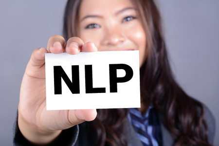 linguistic: NLP letters (or Neuro Linguistic Programming) on the card shown by a woman