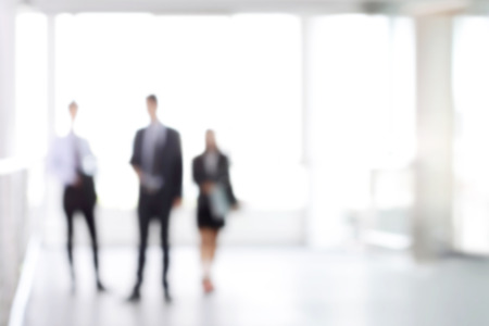 blurred people: Blurred business people standing in white office building hall, can be used as background Stock Photo