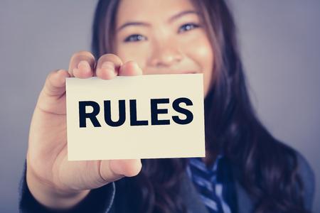 obedecer: Palabra Rules en la tarjeta mostrada por una mujer de negocios, el tono de la vendimia