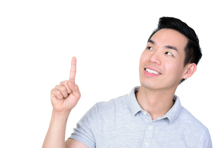 asian guy: Smiling young Asian man looking and pointing up at empty space - isolated on white background Stock Photo