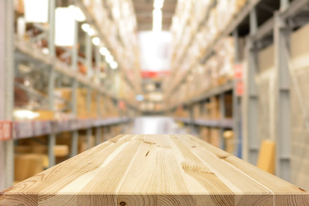 empty warehouse: Empty wood table top (or shelf) on blurred warehouse background