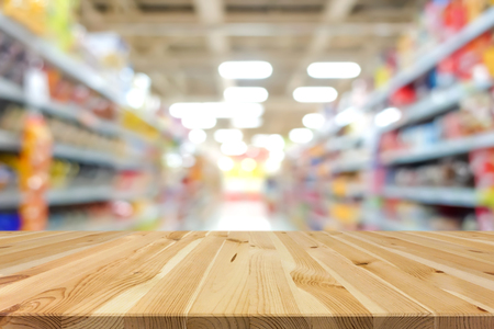 Wood table top on blur supermarket background - can be used for display or montage your products