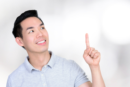 pointing finger up: Smiling young Asian man looking and pointing up, on blur white gray background