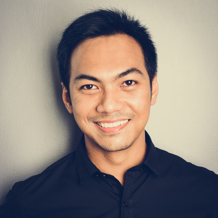 a close up: Attractive smiling Asian man on light gray background - vintage tone effect