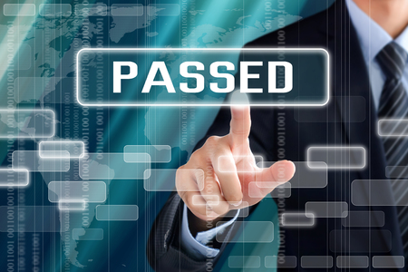 passed test: Businessman hand touching PASSED button on virtual screen