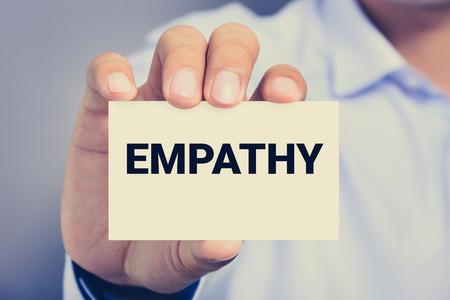 empatia: Mano que muestra la tarjeta con la palabra empatía, efecto del tono de la vendimia