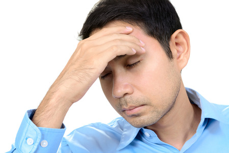 hand on forehead: Young Asian man having headache with hand on his forehead