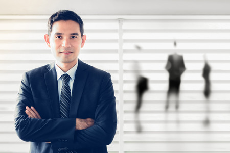 young male: Smiling Asian businessman crossing his arms - leader and success businessman concept Stock Photo