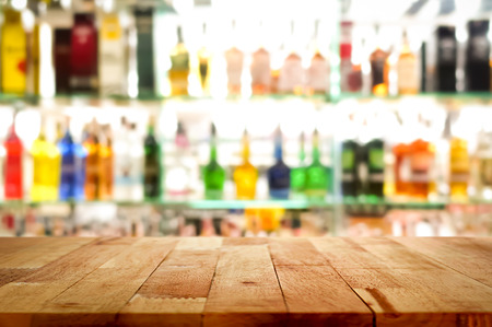 Wood bar top on blur colorful alcohol drink bottle background - can be used for display or montage your products Standard-Bild