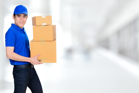 deliveryman: Smiling friendly delivery man carrying parcel boxes on blur white background Stock Photo