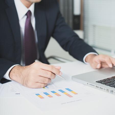 usando computadora: El hombre de negocios que trabajan con ordenador portátil y documentos sobre la mesa - la mano se centró, tono suave Foto de archivo