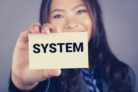 systematic: SYSTEM word on the card shown by a businesswoman, vintage tone effect