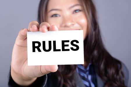 obedecer: Palabra Rules en la tarjeta mostrada por una mujer de negocios