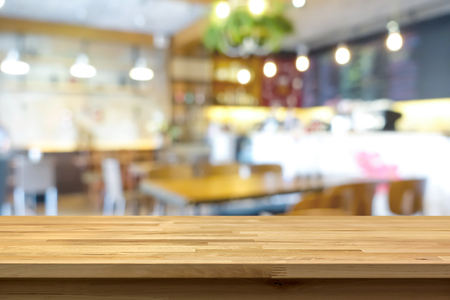 Wood table top on blur background of coffee shop (or restaurant) interior - can be used for display or montage your products Imagens