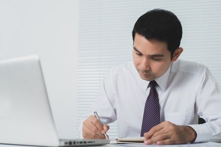 seriously: Handsome Asian businessman working seriously in the office with laptop computer on the table, soft tone