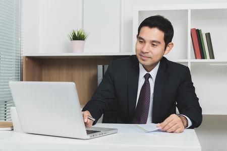 柔らかい音色、セレクティブ フォーカス - オフィスでラップトップ コンピューターを使用してハンサムなアジア系のビジネスマン