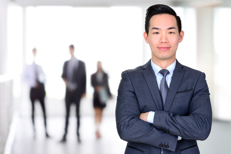 business asia: Smiling Asian businessman crossing his arms - leader and successful businessman concept