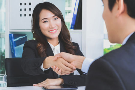Asian businesswoman making handshake with a businessman in the office, soft tone Фото со стока