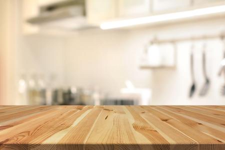 Dessus de table en bois (en tant qu'hôte de cuisine) sur un fond intérieur de cuisine flou - peut être utilisé pour l'affichage ou le montage de vos produits