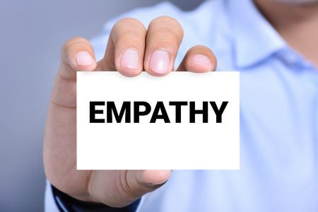 empatia: Mano que muestra la tarjeta con la palabra EMPATÍA