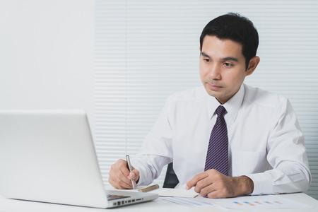 hombres trabajando: Hombre de negocios asiático hermoso que trabaja en la oficina con el ordenador portátil y documentos sobre la mesa, el tono suave Foto de archivo