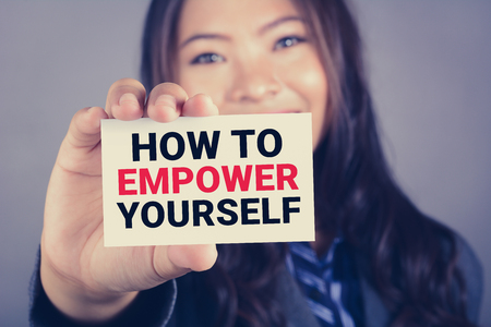 empower: HOW TO EMPOWER YOURSELF message on the card shown by a businesswoman, vintage tone effect