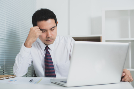 Asian businessman getting stressed at work in front of laptop computer - soft tone Stock Photo