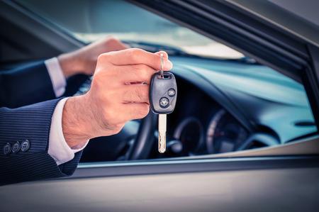 auto leasing: Businessman hand showing a car key - car sale & rental business concept