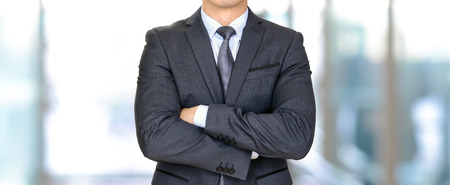 businessman suit: Anonymous businessman in dark gray suit crossing his arms - panoramic header business background Stock Photo