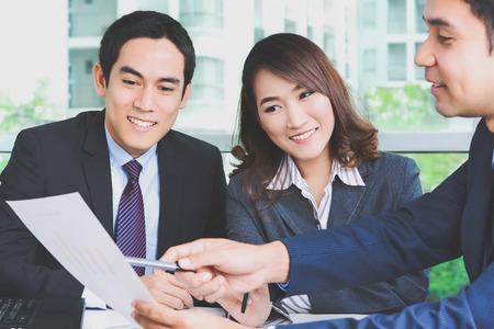 Asiatische Geschäftsleute Dokument in einer Sitzung diskutieren