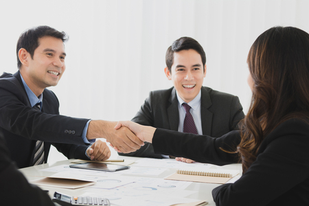 agree: Smiling businessman making handshake with a businesswoman in the meeting