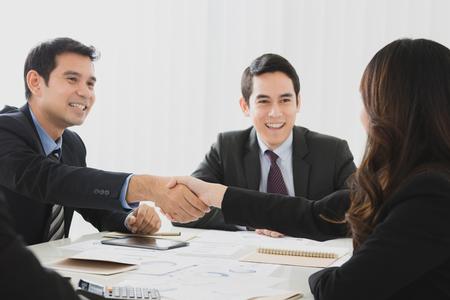 coincidir: Sonriente hombre de negocios haciendo apretón de manos con una mujer de negocios en la reunión