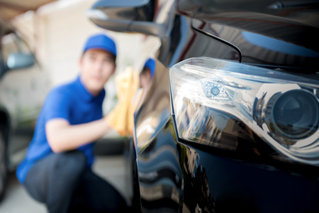 dry cleaners: Car (auto) cleaning staff cleaning car - selective focus Stock Photo