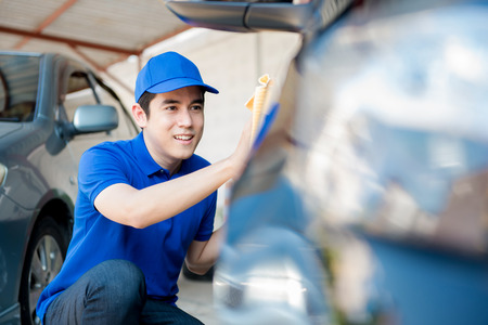 valeting: A man polishing (cleaning) car, auto detailing or valeting concept