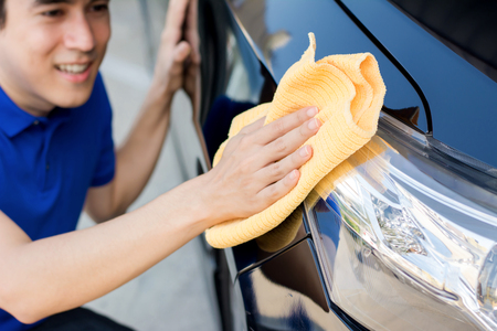 valeting: A man polishing (cleaning) car with microfiber cloth, car detailing or valeting concept