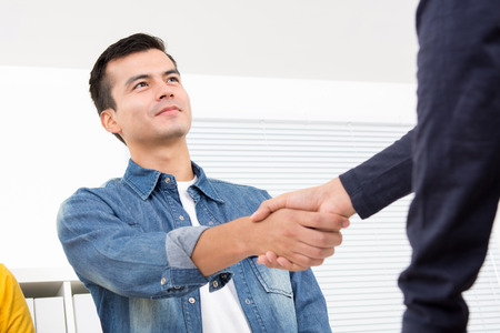 casual: Handsome man wearing casual jean shirt making handshake in the office Stock Photo