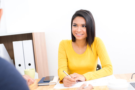 filipino adult: Smiling Asian woman wearing casual yellow t-shirt in the meeting - businesswoman and entrepreneur concepts Stock Photo