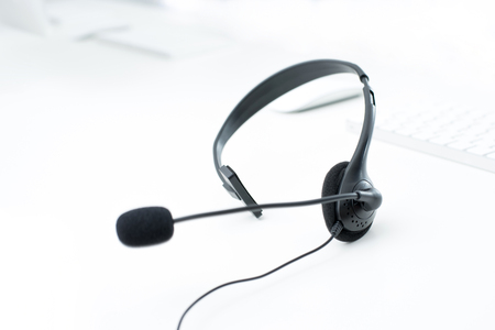 operator: Microphone headset on white table with blur computer keyboard background - operator, call center,customer service and telemarketing concepts