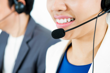 telemarketer: Smiling woman wearing microphone headset as an operator (or telemarketer) - call center and customer service concepts