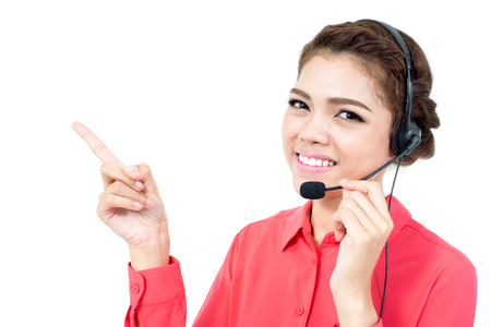blank center: Young businesswoman  wearing microphone headset as an operator pointing her hand to blank space Stock Photo