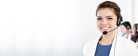 Lächelnde Frau mit Mikrofon-Headset als Operator, Telemarketer, Call Center und Customer Service-Mitarbeiter - Panorama-Hintergrund oder Banner mit Leerzeichen